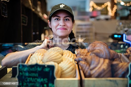 Morning routine for millennial latino bread maker in her own business place putting freshly made croissants and conchas in window display in early morning. She is looking at the camera with a proud face. Horizontal waist up shot with copy space.