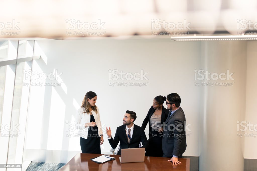 Millennial business man showing partners work on laptop stock photo