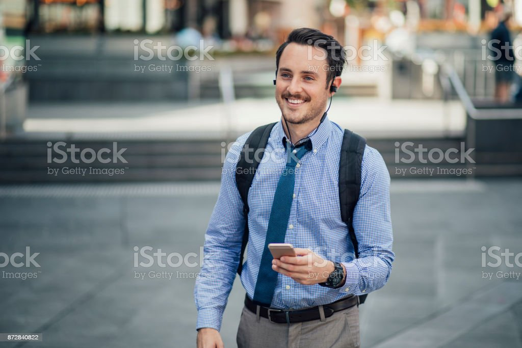 Millennial Businessman Commuting In Melbourne Happy millennial businessman is commuting in Melbourne, Victoria with a smartphone, listening to music through his earphones. 20-29 Years Stock Photo