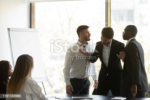 Millennial businessman setting apart two aggressive multiracial coworkers, starting fighting at office. Mixed race young colleagues quarreling shouting at each other, misbehaving during meeting.