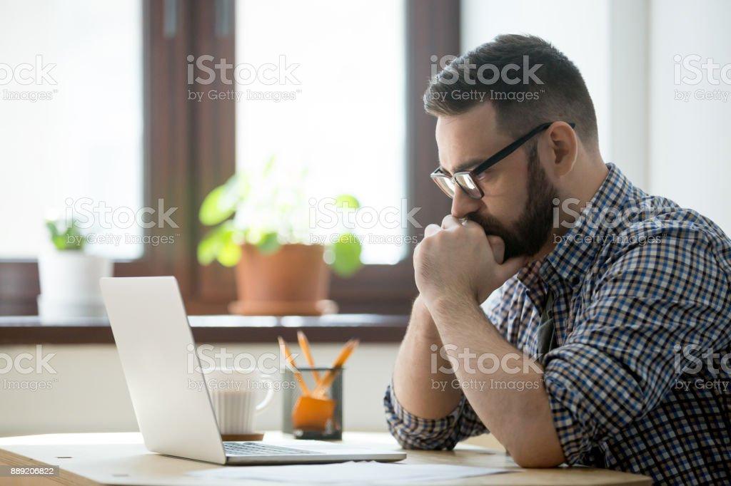 Empresario informal milenario pensando y mirando la laptop en la oficina - Foto de stock de Adulto libre de derechos