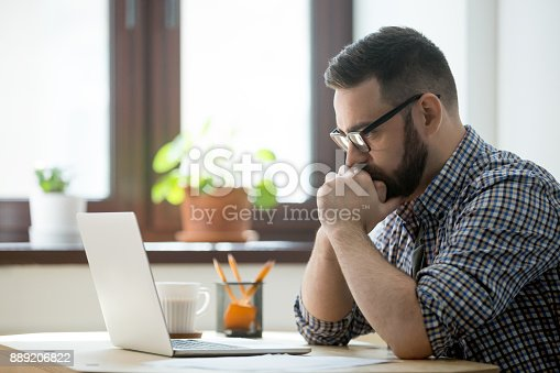 istock Millennial casual businessman thinking and looking at laptop in office 889206822