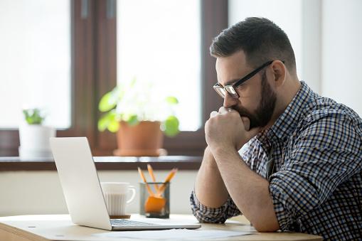 Empresario Informal Milenario Pensando Y Mirando La Laptop En La Oficina Foto de stock y más banco de imágenes de Adulto