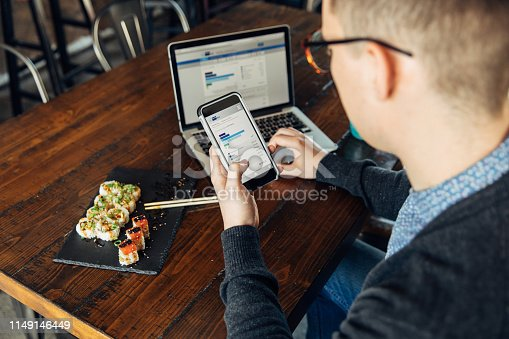 A man of the Millennial Generation is looking at his financial statement while eating lunch at a local sushi restaurant. He is using his bank's app on his smart phone and laptop to balance his monthly budget and plan for the future. Image taken in Utah, USA.