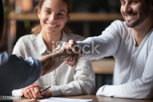 istock Millennial cheerful business people shaking hands sitting indoors 1172964234