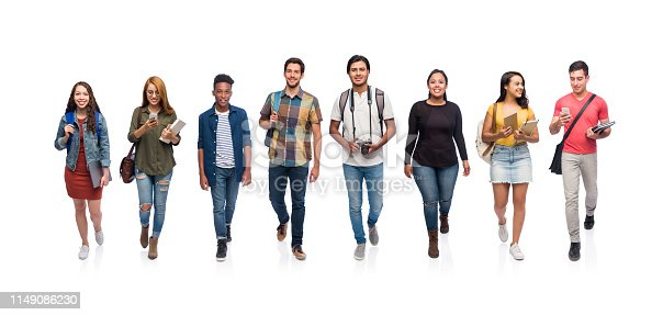 Full body photo of a group of millennial college students walking together towards the camera at the same time.
