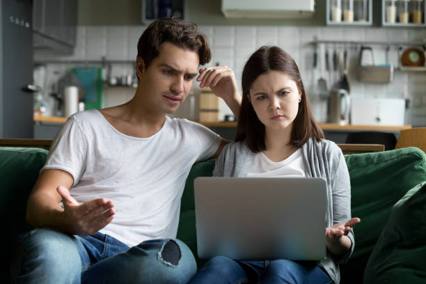 Millennial couple annoyed by stuck laptop confused by online news stock photo