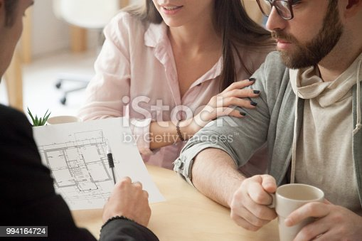 istock Millennial couple consulting about home design project in architect office 994164724
