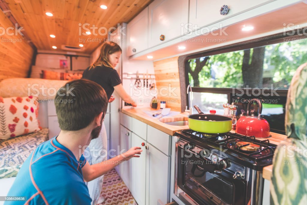 Millennial couple cook breakfast in the van they live in A young couple live in a van. They're making breakfast and she is standing by the sink while he reaches to pick something up off the counter. Adults Only Stock Photo