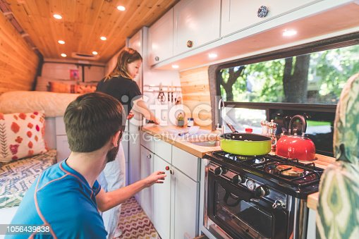 A young couple live in a van. They're making breakfast and she is standing by the sink while he reaches to pick something up off the counter.