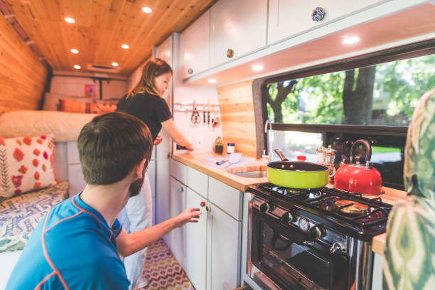 Millennial couple cook breakfast in the van they live in A young couple live in a van. They're making breakfast and she is standing by the sink while he reaches to pick something up off the counter. rv interior stock pictures, royalty-free photos & images