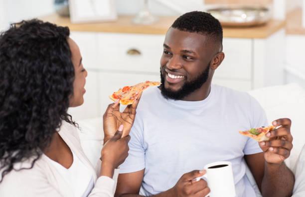 pareja milenaria comiendo pizza y bebiendo café, relajante en casa - happy couple sharing a cup of coffee fotografías e imágenes de stock