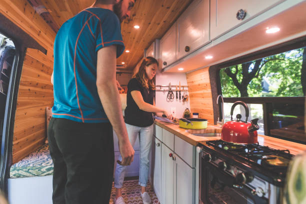 Millennial couple living in a van A young couple live in a van. The side door is open and she is chopping vegetables as he stands by the stove and gets ready to pull out tablewear. rv interior photos stock pictures, royalty-free photos & images