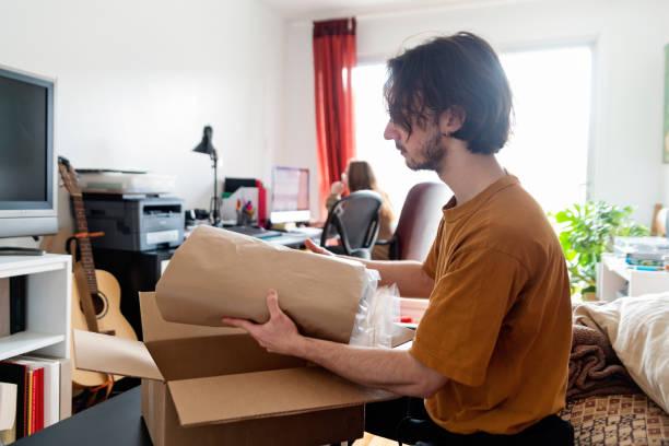 Jahrtausende lange Ehepaar öffnet ein angeliefertes Paket im Wohnzimmer. – Foto