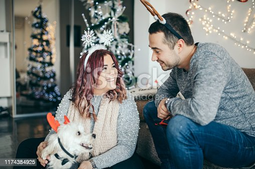 Millennial couple playing with cute dog