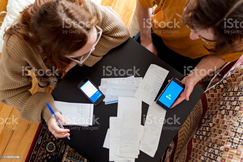 Real millennial couple of students sharing life and resources in...