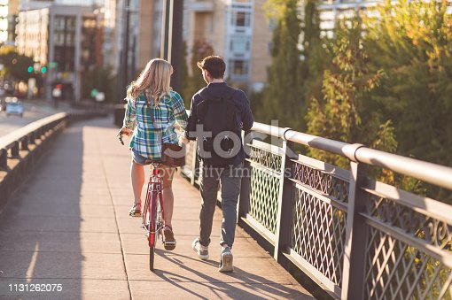 A cute couple in their 20s walks along a city bridge together. She is riding a bicycle and he is steadying it while she rides it. There is traffic going by on the left and city buildings in the background.
