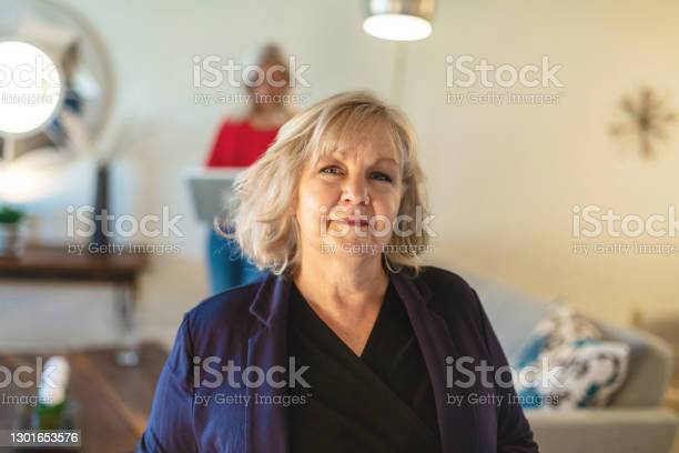 Millennial Daughter And Mature Adult Mother In Living Room Setting Mothers Day Photo Series Stock Photo - Download Image Now