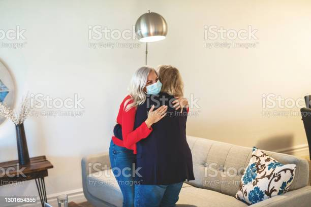 Millennial Daughter And Mature Adult Mother Visiting In Living Room Setting During Pandemic Mothers Day Photo Series Stock Photo - Download Image Now
