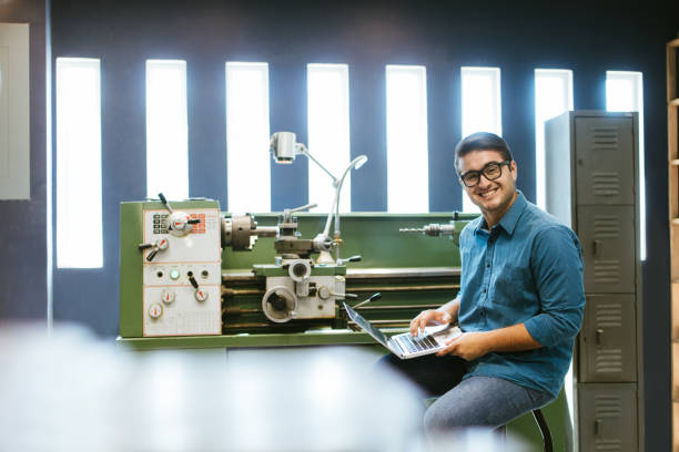 Millennial engineer working on laptop in shop stock photo