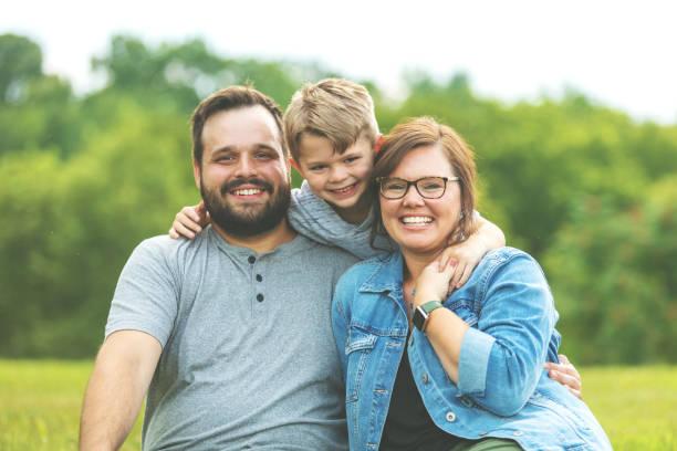 millennial vater und mutter mit autistischen kind in öffentlichen üppigen grünen park sitzt auf dem gras lächelnd pose für familienporträt - autismus stock-fotos und bilder