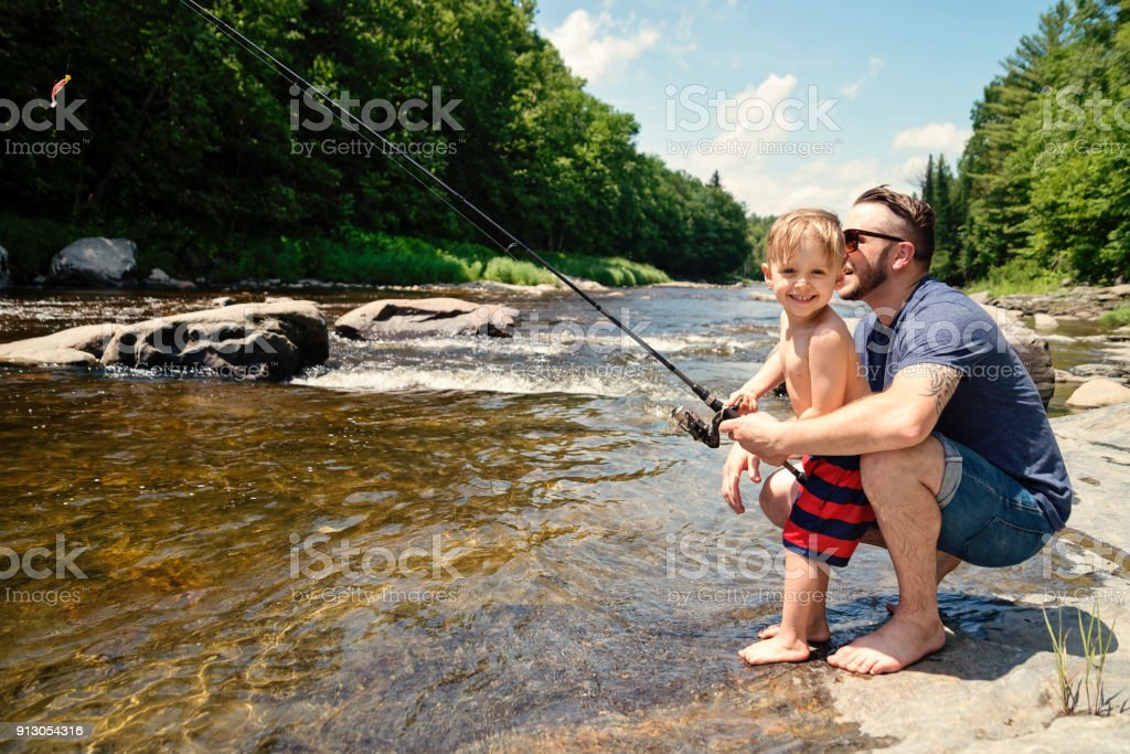 Millennial father showing son how to fish in a river in summer nature. stock photo