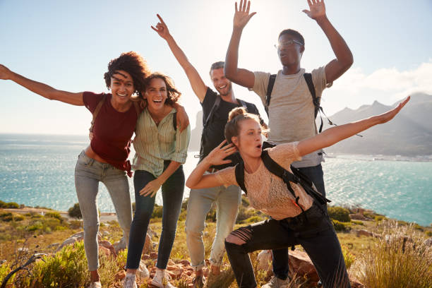 Millennial friends on a hiking trip celebrate reaching the summit and have fun posing for photos stock photo