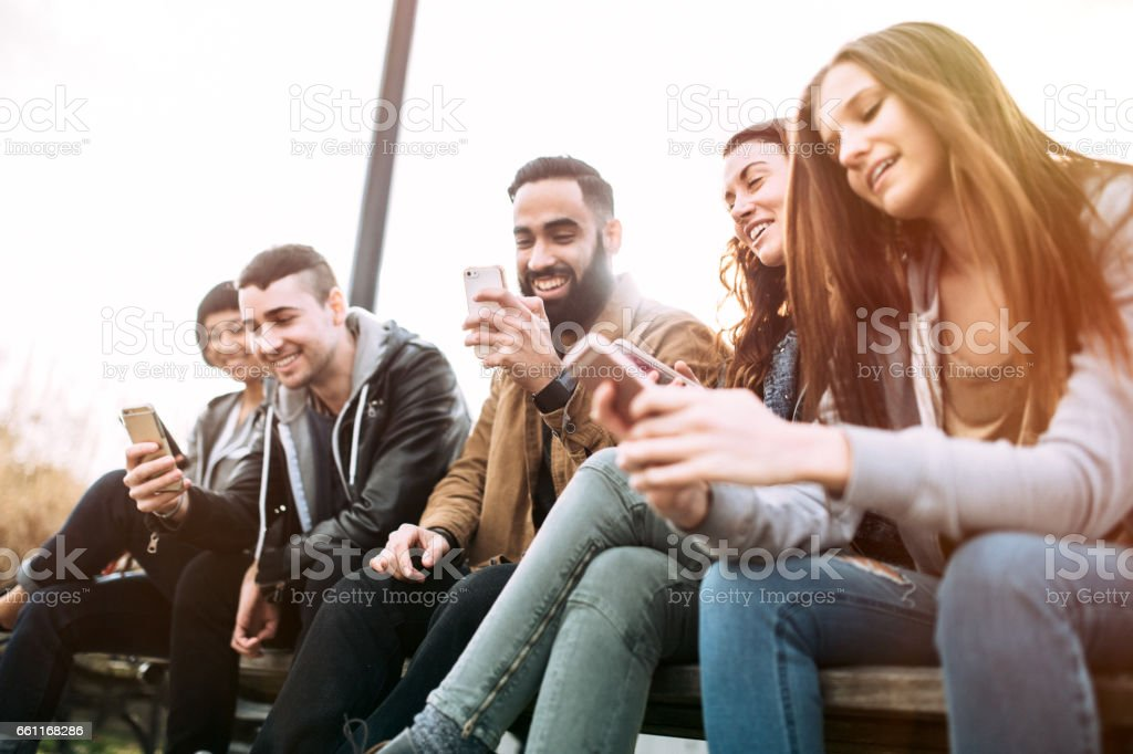 Amigos milenarios en teléfonos inteligentes - foto de stock