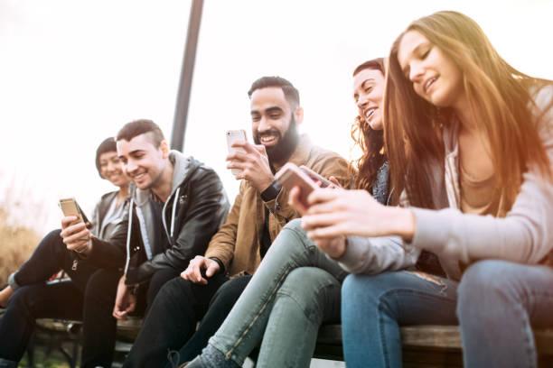 amigos milenarios en teléfonos inteligentes - generación del milenio fotografías e imágenes de stock