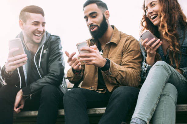 millennial friends on smart phones - millennial generation stock photos and pictures