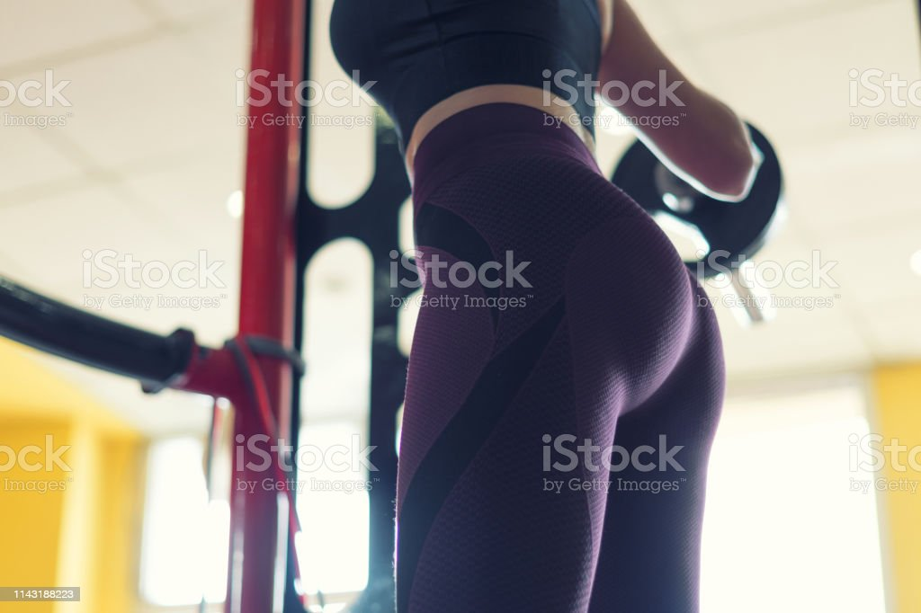 Close up of Young blonde girl training in the gym. Bodybuilding.