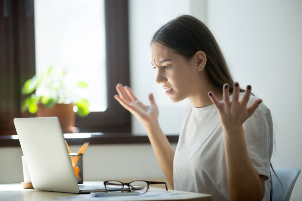 Millennial generation woman looking in laptop computer, fling arms  up stock photo
