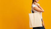 No To Plastic. Unrecognizable Girl Carrying White Eco Bag Over Yellow Background. Studio Shot, Copy Space, Cropped