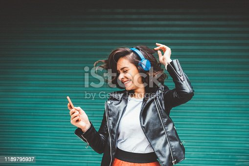 Beautiful woman dancing to the music against coloured wall