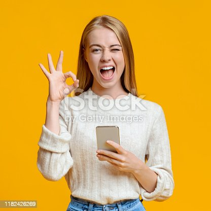 Beautiful millennial girl holding smartphone, winking and gesturing ok over orange studio background, copy space