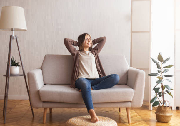 Millennial girl relaxing at home on couch Millennial girl relaxing at home on couch, enjoying weekends, empty space relaxation stock pictures, royalty-free photos & images