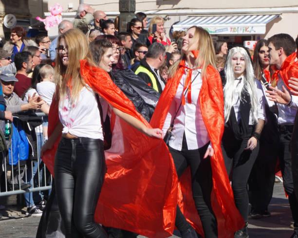 jahrtausende mädchen mit rotem mantel tanzen auf der straße in karnevalsparade - cro maske stock-fotos und bilder