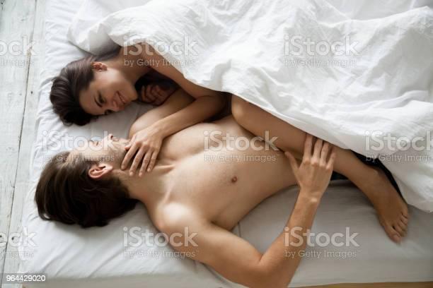 Foto de Casal Feliz Milenar Relaxante Juntos Deitado Na Cama Acariciando e mais fotos de stock de Abraçar