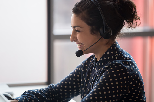 Happy young indian female call center agent wearing headset and consulting client online. Positive woman worker with earphones helping to solve customer problems close up.