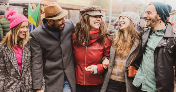 Millennial hipsters walking on the street of London - Friendship and freedom concept - Happy multiethnic friends walking in town and celebrating - Desaturated Filter - Focus on Hats. Fun Together stock photo