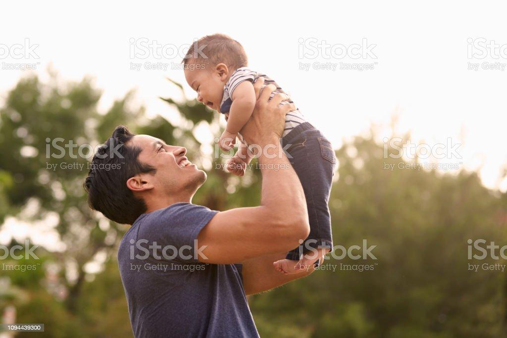 Millennial Hispanic father holding his little baby in the air in the park, close up Millennial Hispanic father holding his little baby in the air in the park, close up 20-29 Years Stock Photo