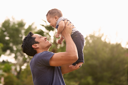 Millennial Hispanic Father Holding His Little Baby In The Air In The Park Close Up Stock Photo - Download Image Now