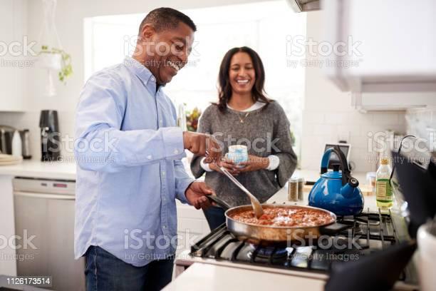 Millennial hispanic man standing in the kitchen cooking with his picture id1126173514?b=1&k=6&m=1126173514&s=612x612&h=udnxnggbfwvewfil6x0gcdrd5k9lfru3ru5gy83keau=