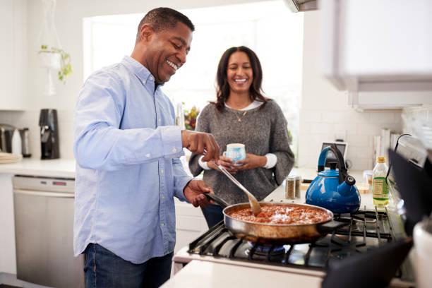 uomo ispanico millenario in piedi in cucina cucina con il suo compagno in piedi accanto a lui, retroilluminato - cucinare foto e immagini stock