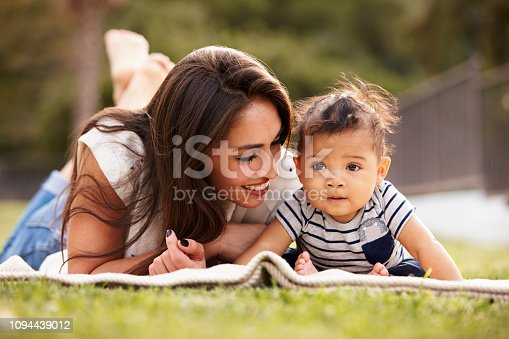 istock Millennial Hispanic mother lying on a blanket in the park with her baby smiling, close up 1094439012