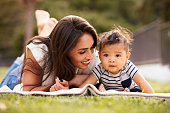 Millennial Hispanic mother lying on a blanket in the park with her baby smiling, close up