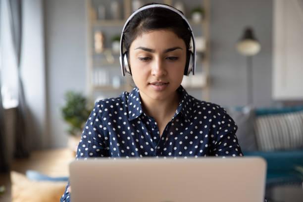 Millennial indische Mädchen in Kopfhörer Studie auf Laptop – Foto