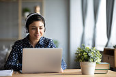 Millennial Indian girl in wireless headphones sit at desk at home working on modern laptop, young ethnic woman in earphones browsing Internet shopping online or studying on computer in living room