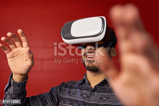 istock Millennial Indian man exploring space with virtual reality glasses in 613113582