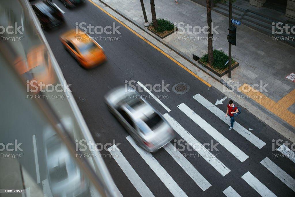 Millennial Korean man crossing busy street